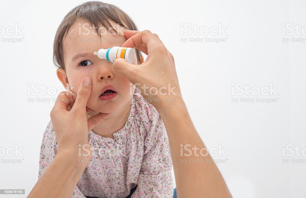 Mother pouring eye drops in the eye of her daughter stock photo