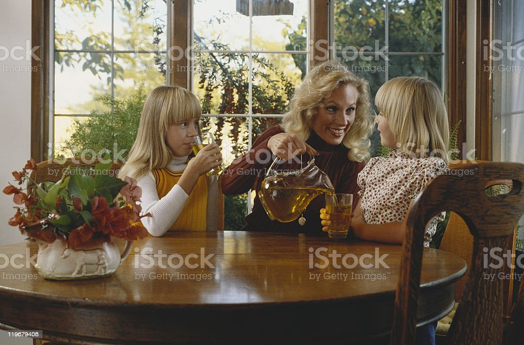 Mother pouring juice for daughter royalty-free stock photo