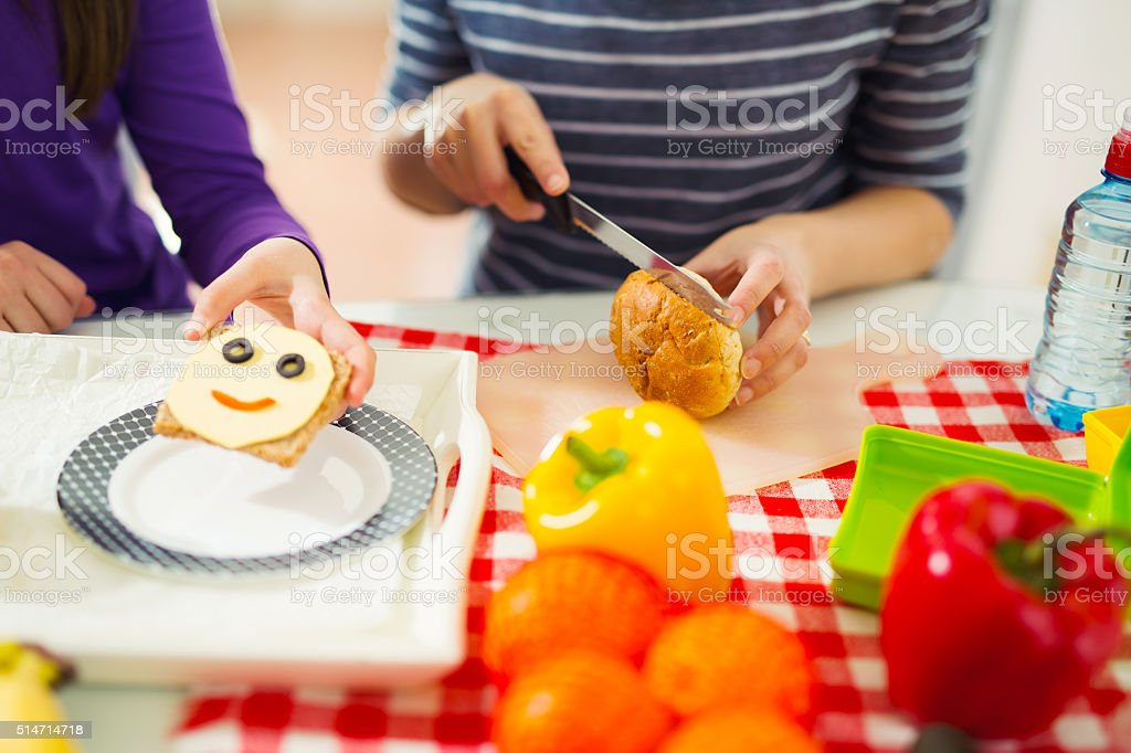 Mother preparing healthy and tasty lunch box for child stock photo