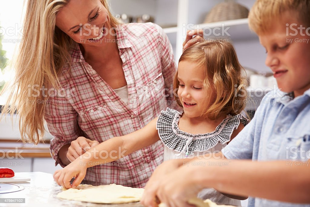 Mother preparing pizza with kids stock photo
