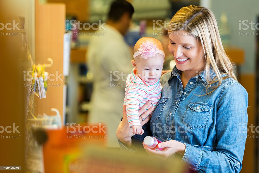 Mother purchasing cold & fever medicine for infant daughter stock photo