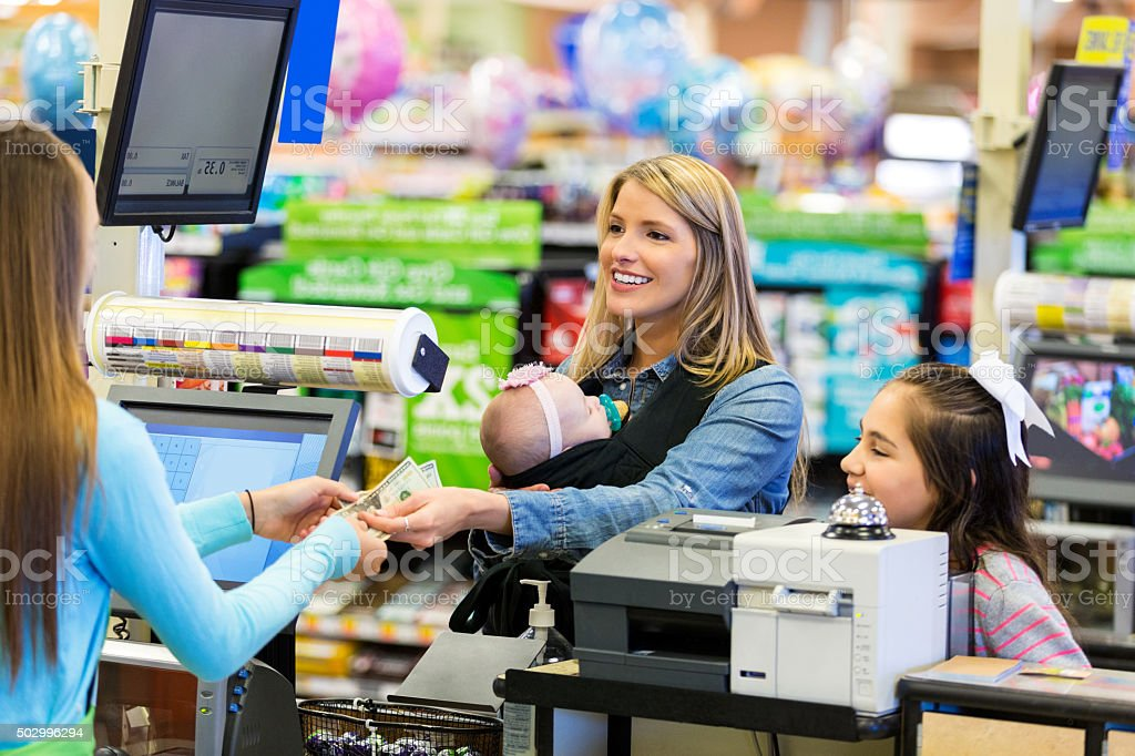 Mother purchasing groceries while shopping with daughters stock photo