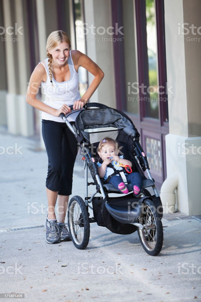 Mother pushing baby stroller on sidewalk stock photo
