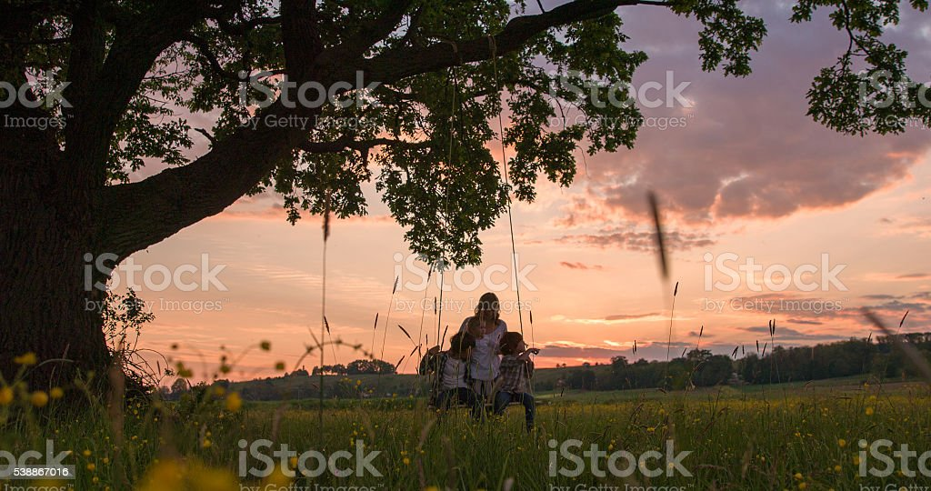 Mother pushing children on swing during sunset stock photo
