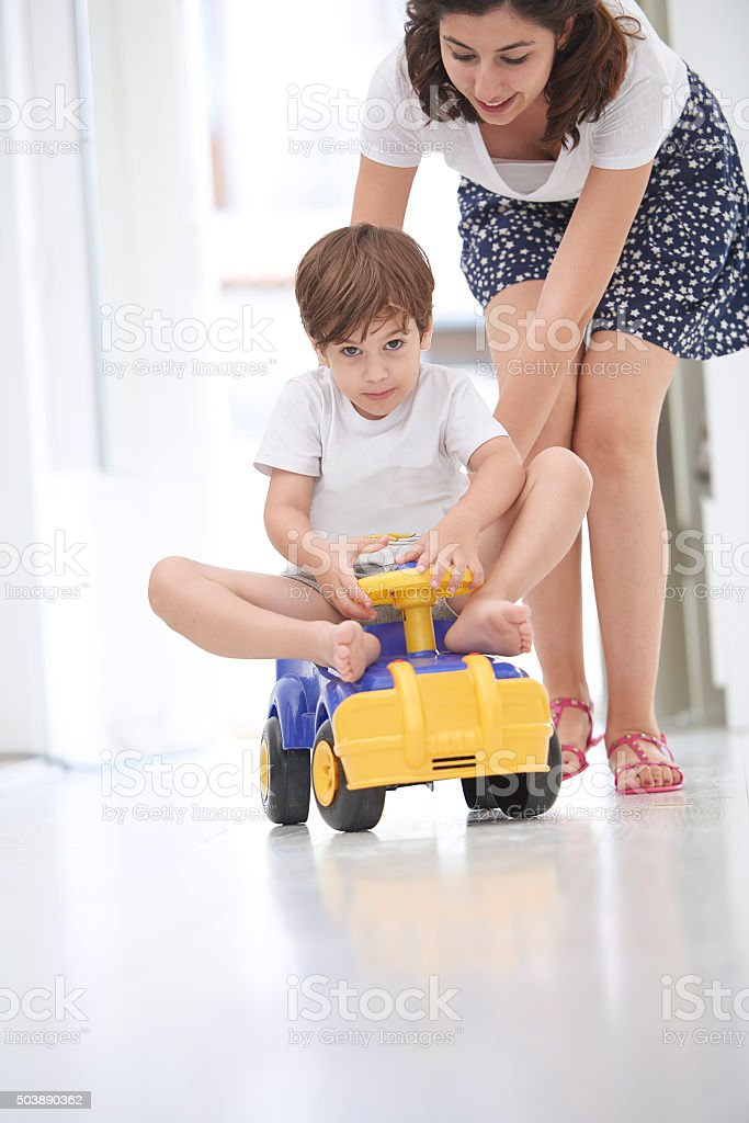 Mother pushing daughter in toy car stock photo