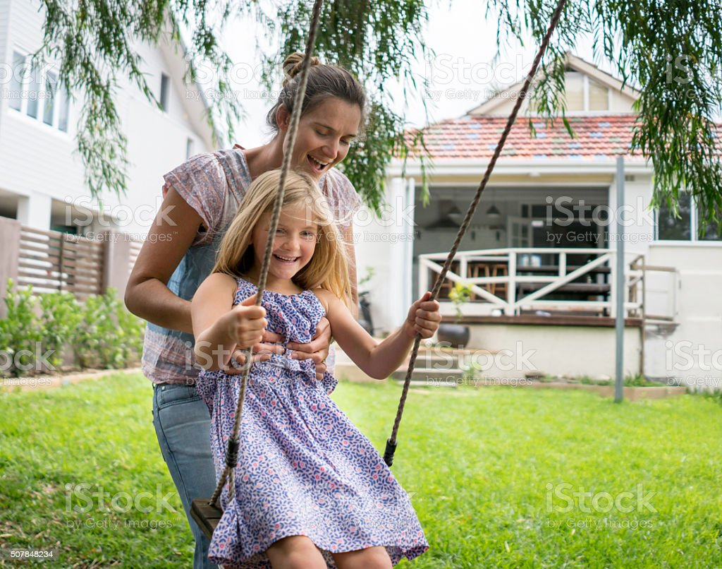 Mother pushing daughter on a swing stock photo