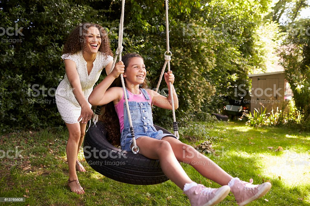 Mother Pushing Daughter On Tire Swing In Garden stock photo