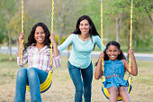 Mother pushing her daughters on swings