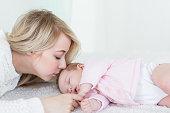 mother puts her baby daughter to sleep