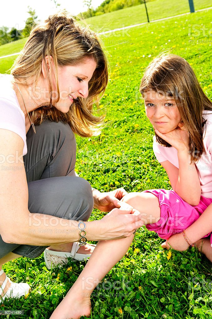 A mother putting a plaster in a child's knee outside stock photo