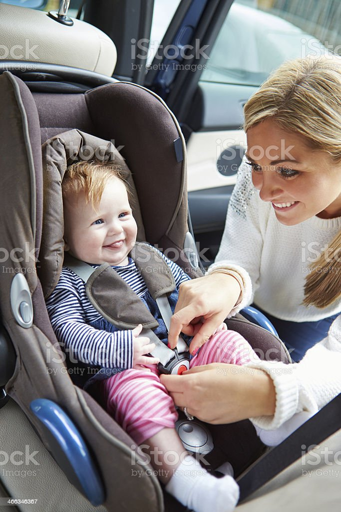 Mother Putting Baby Into Car Seat stock photo