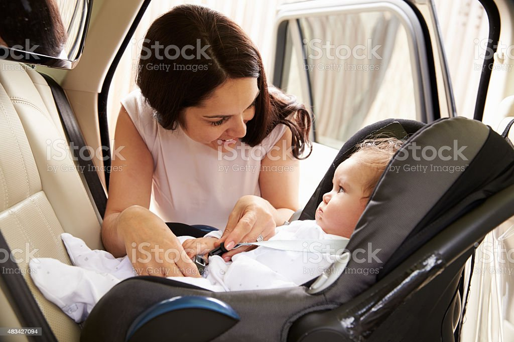 Mother Putting Baby Son Into Car Travel Seat stock photo