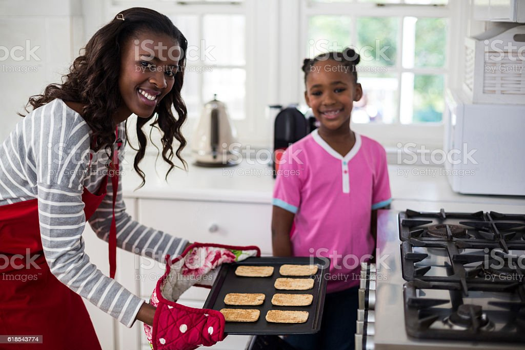 Mother putting baking tray in oven stock photo