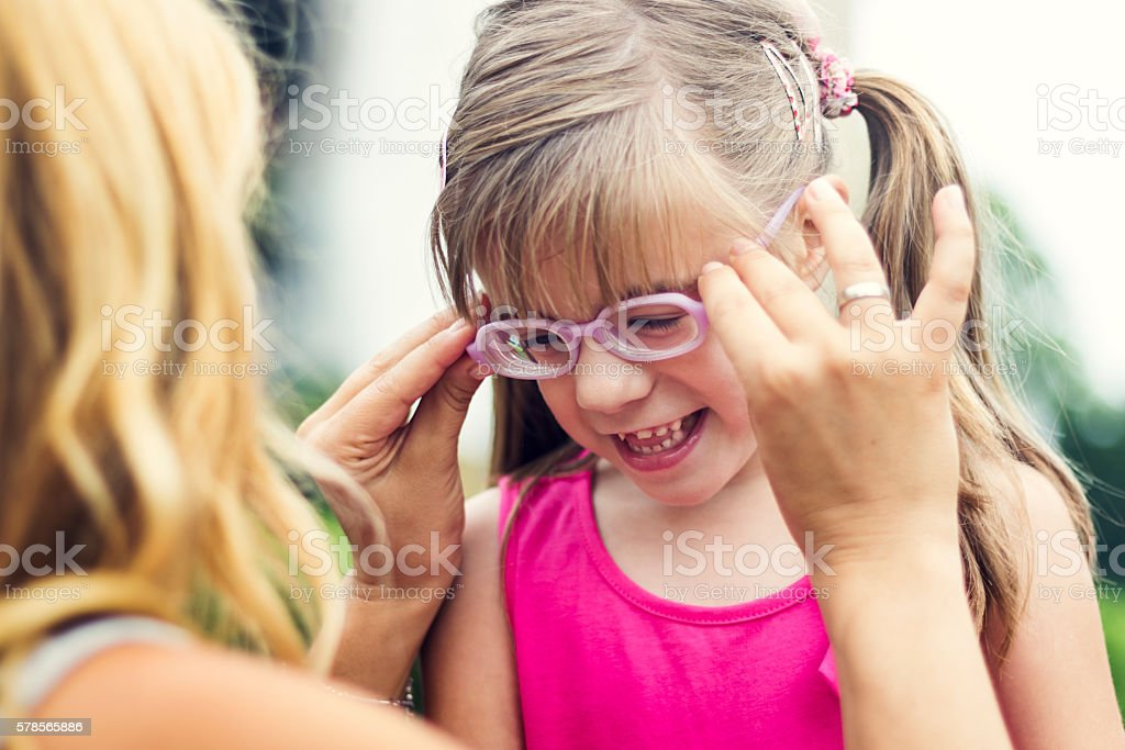 Mother putting eyeglasses on her daughter outdoors stock photo