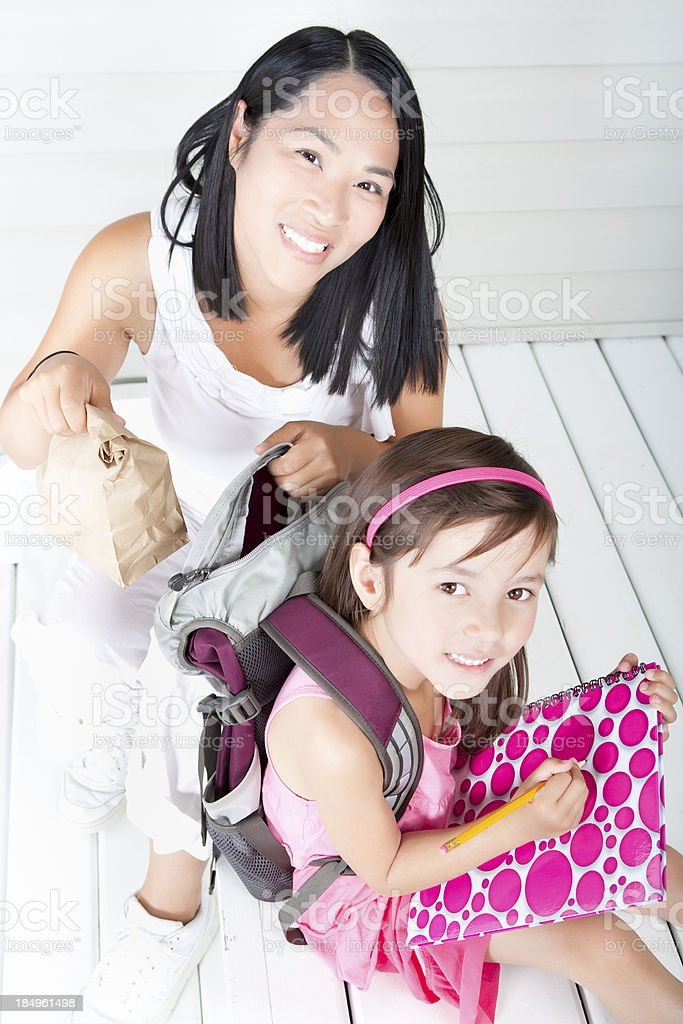 Mother putting lunch bag in girl student backpack outdoor royalty-free stock photo