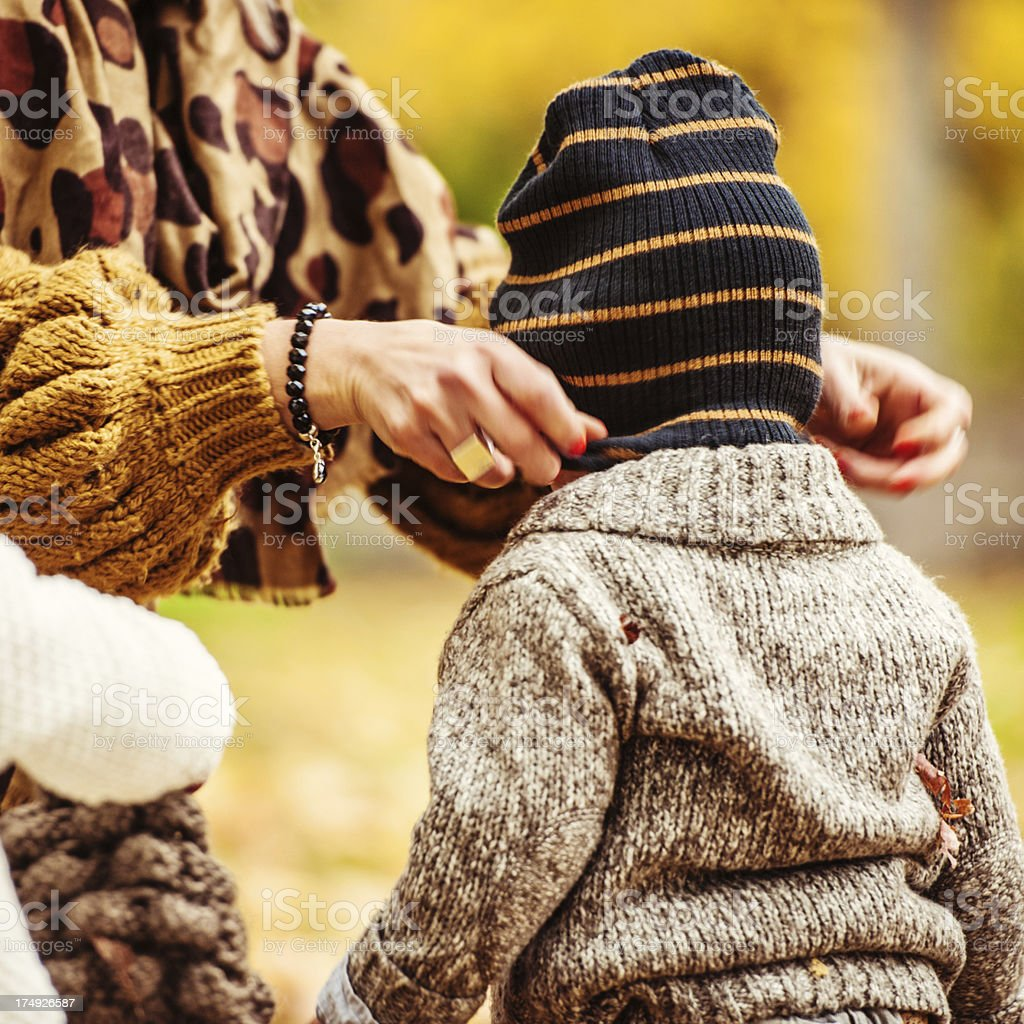 Mother putting on son hat royalty-free stock photo