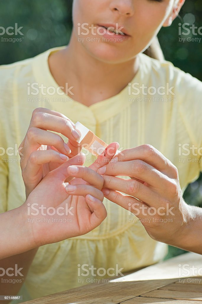 Mother putting plaster on childs finger royalty-free stock photo