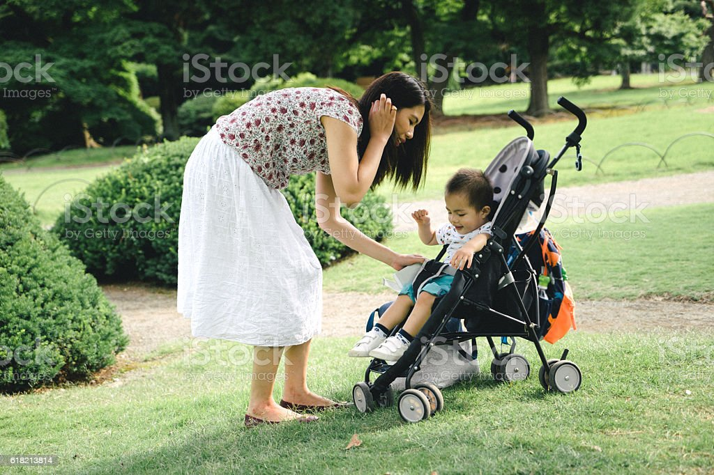 Mother putting son in stroller outdoors, park on the background stock photo