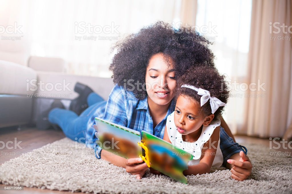 Mother reading a book to her daughter on carpet stock photo
