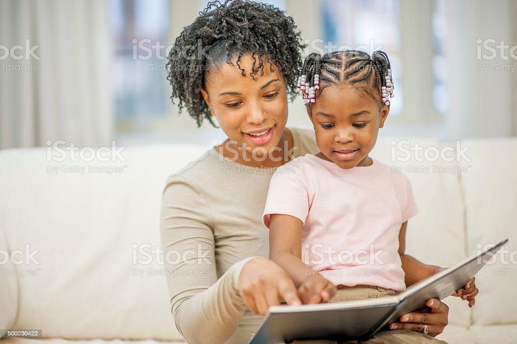 Mother Reading a Book to Her Little Girl stock photo