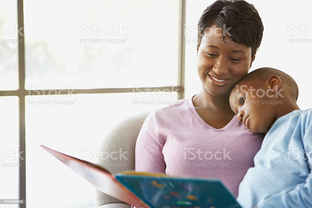 Mother reading a story to her son stock photo