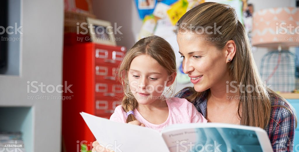 Mother Reading Book With Daughter In Bedroom stock photo