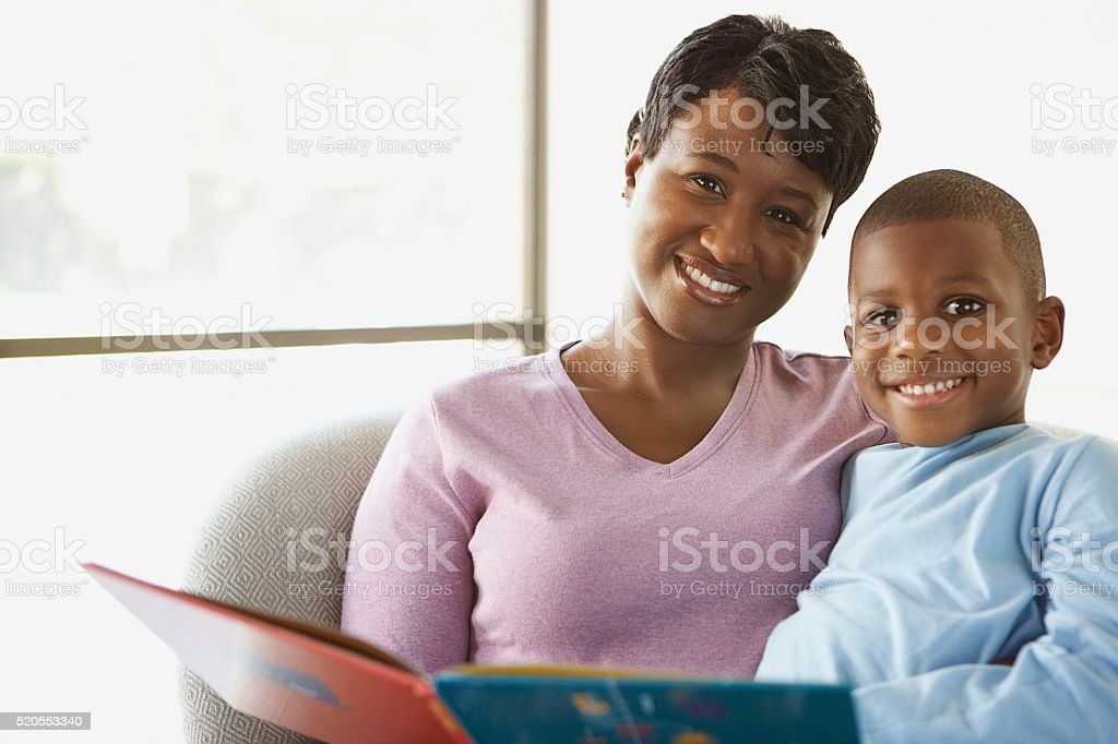 Mother reading stories to her son stock photo