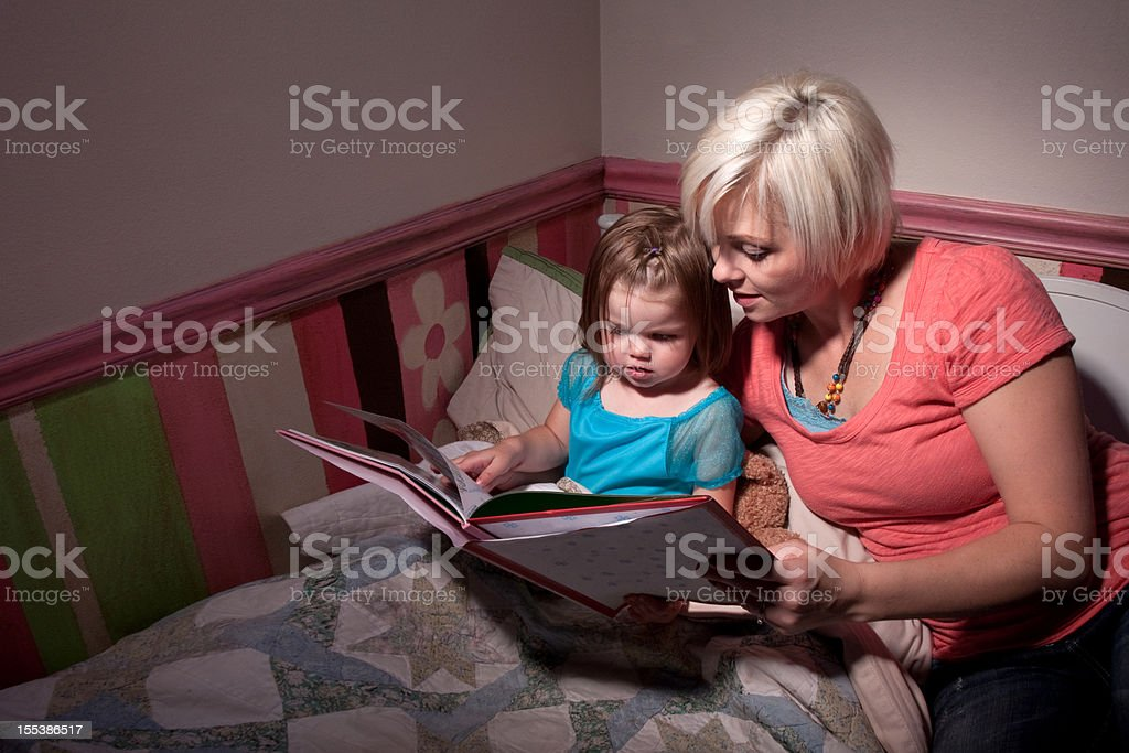 Mother Reading Story to Child in Bed stock photo