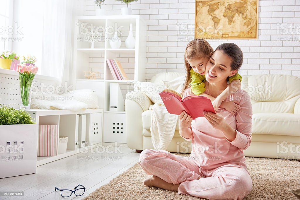mother reading to daughter stock photo