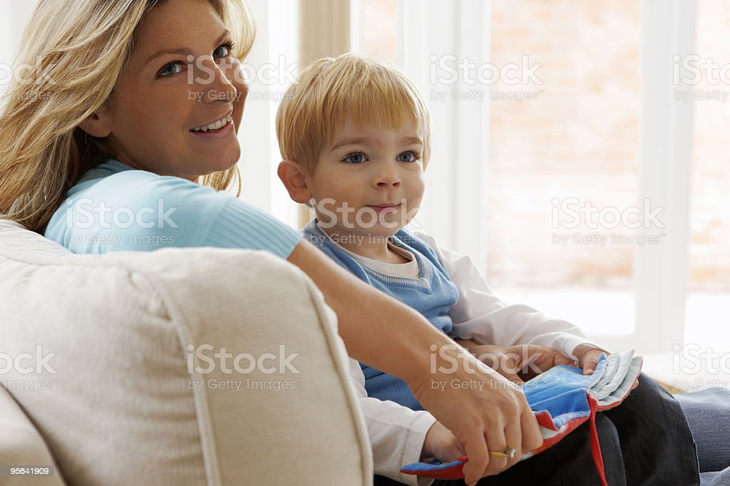 Mother reading to her son on the sofa at home royalty-free stock photo