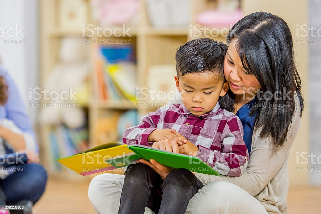 Mother Reading to Her Son stock photo