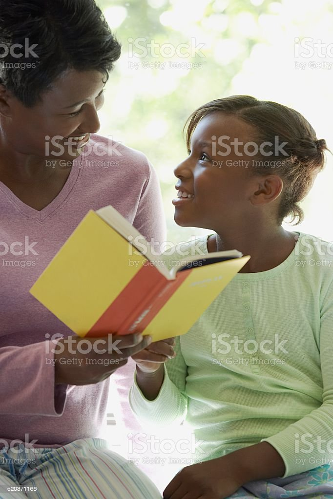 Mother reading with her daughter stock photo