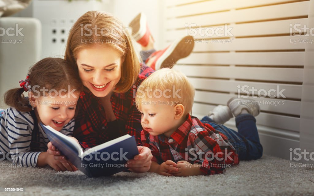 Mother reads book to children stock photo