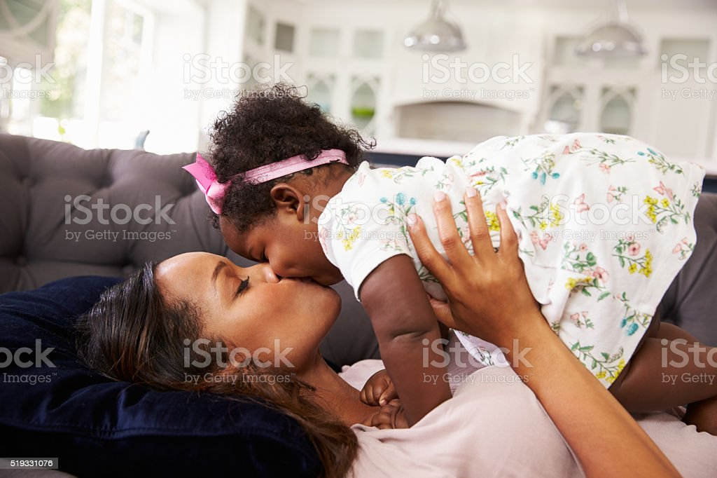 Mother reclining, holding and kissing her toddler daughter stock photo