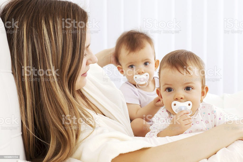 Mother resting with two cute babies girl twins in bedroom. royalty-free stock photo