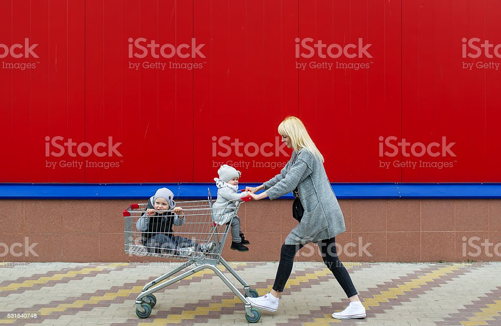 Mother rolls in the cart of children. stock photo