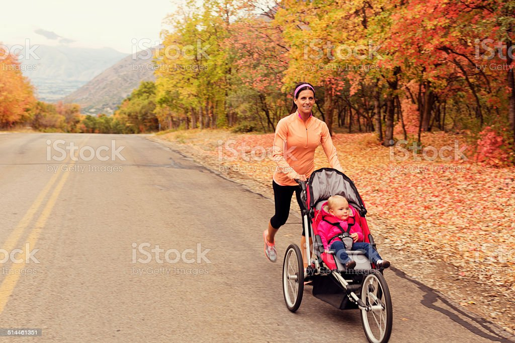 Mother Running with Daugter in Jogging Stroller stock photo