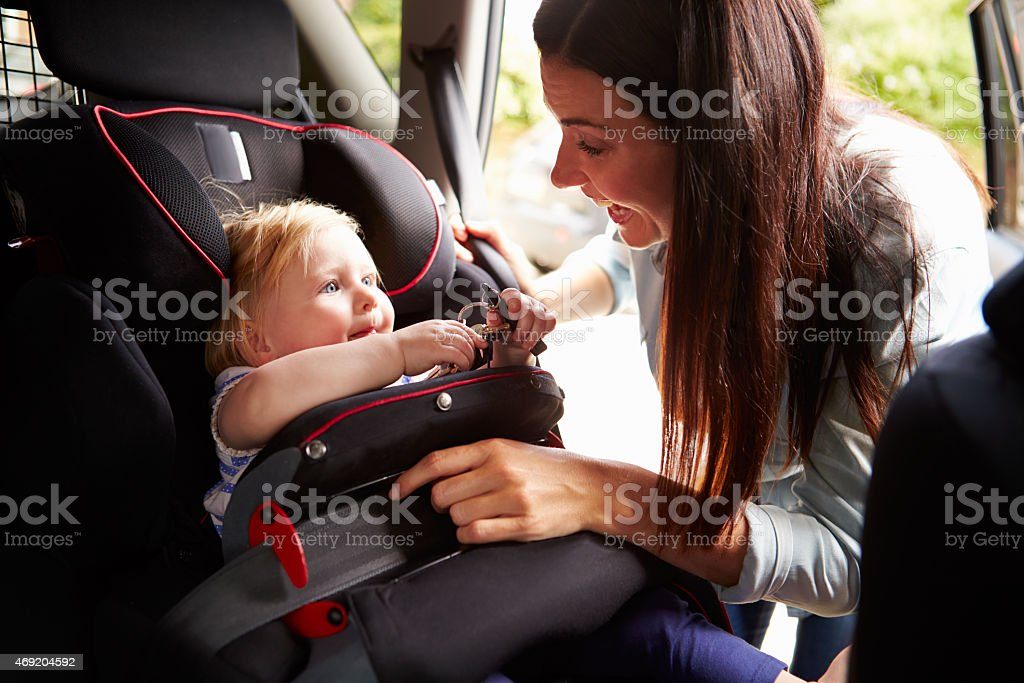 Mother securing infant daughter in car seat stock photo