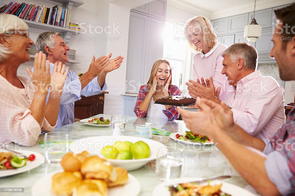 Mother Serves Birthday Cake To Adult Daughter At Family Meal stock photo