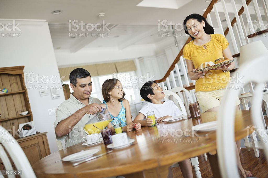 Mother Serving Breakfast With Family Sitting At Table royalty-free stock photo