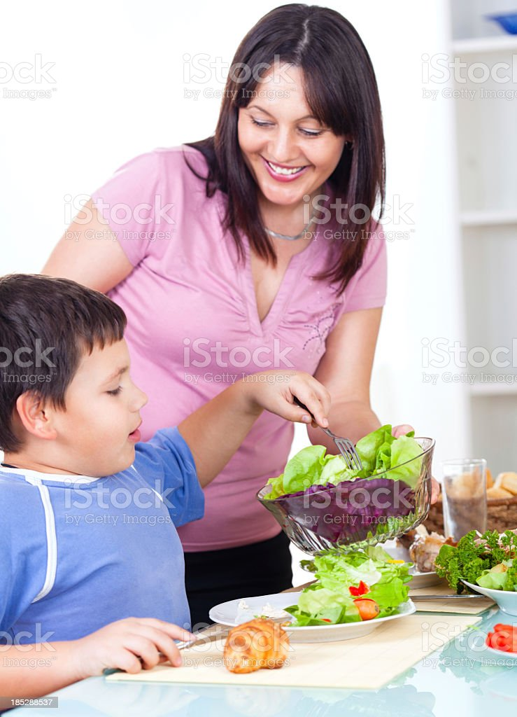 Mother serving fresh healthy salad to her son stock photo