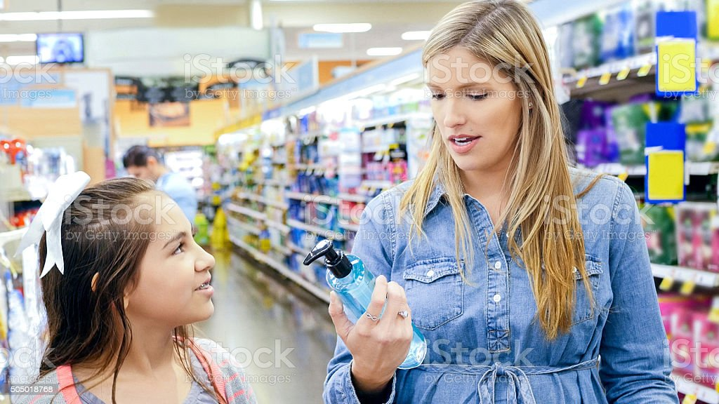 Mother shopping for beauty products with young daughter in store stock photo