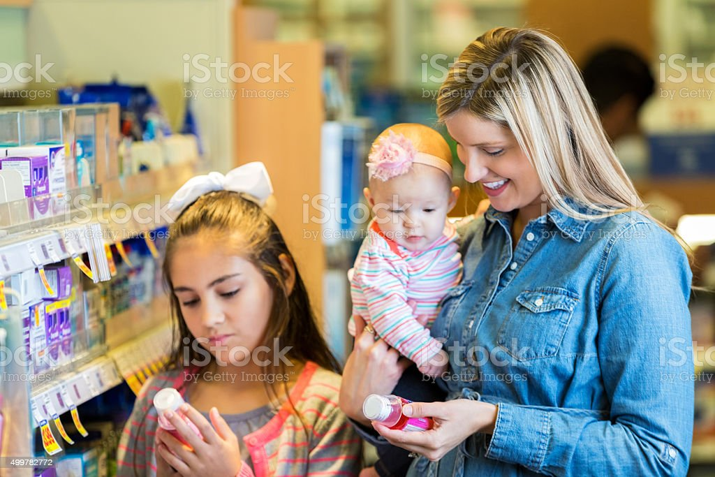 Mother shopping for children's medicine in pharmacy with daughters stock photo