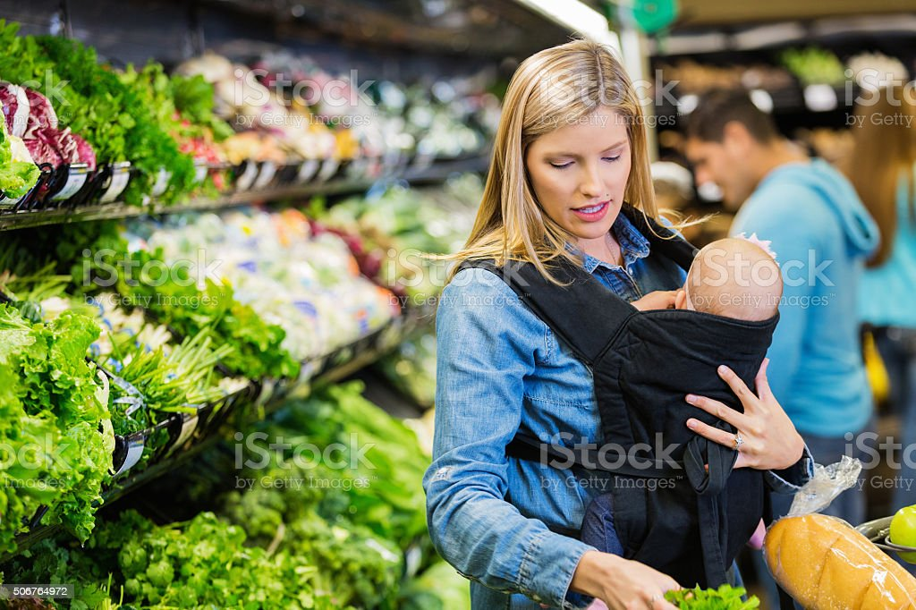 Mother shopping with infant daughter in grocery store or supermarket stock photo