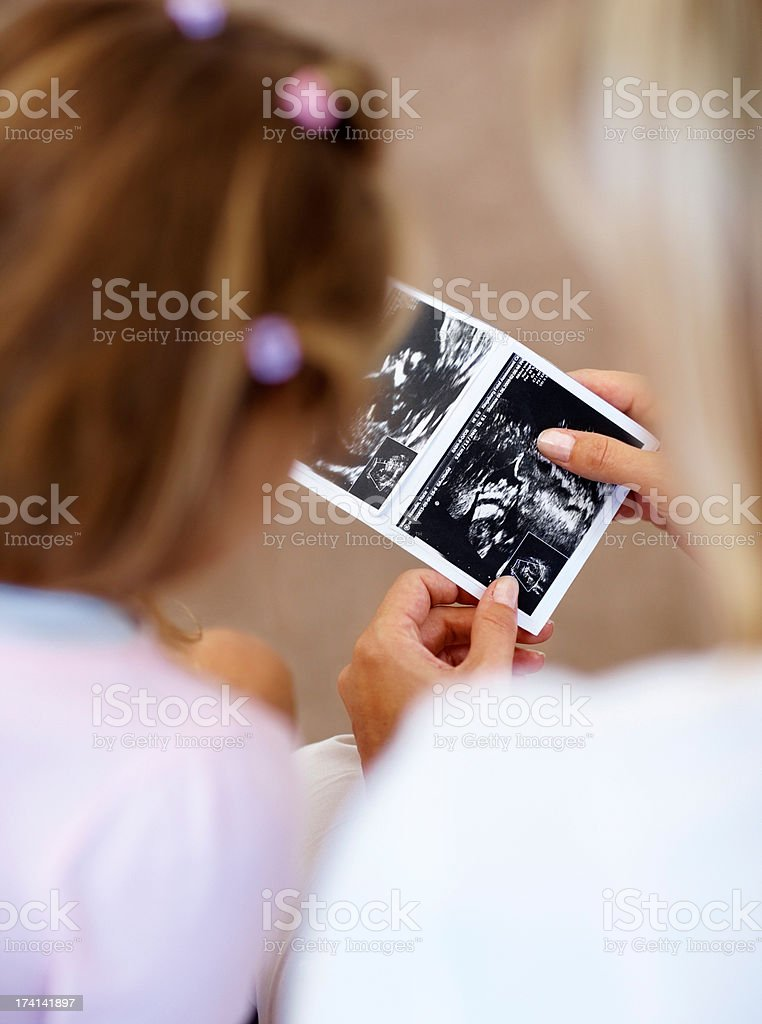 Mother showing sonogram of her unborn child to her daughter royalty-free stock photo