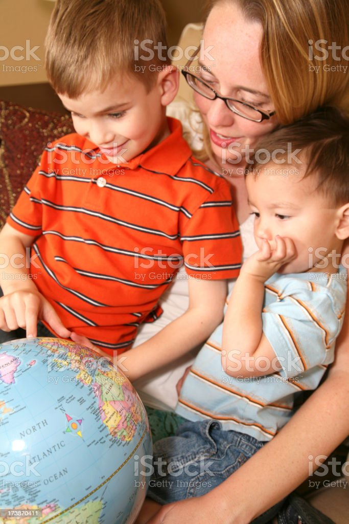 Mother Showing Two Sons a Globe royalty-free stock photo