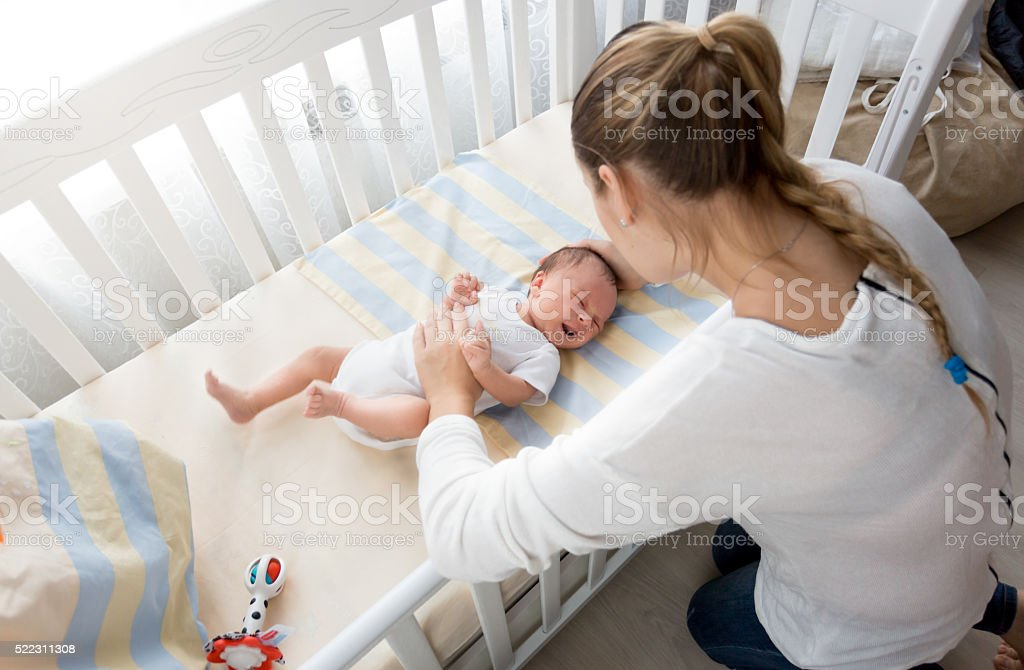 Mother sitting near the cradle and holding baby's hand stock photo