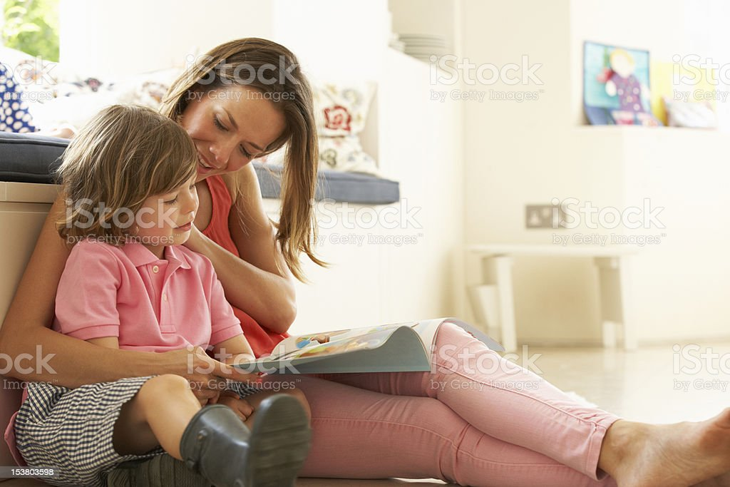 Mother Sitting With Son Reading Story Indoors stock photo