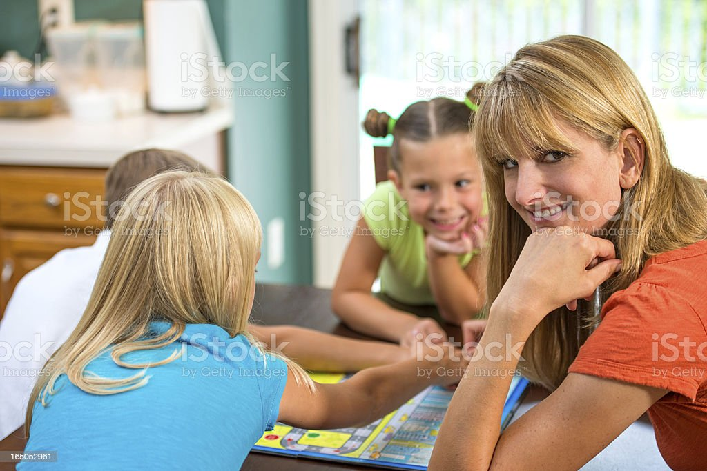 Mother Smiles During Play Date Children Playing Board Game stock photo