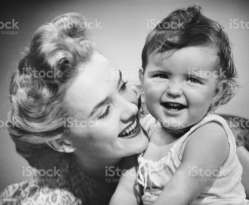Mother smiling to baby girl (12-18 months), (B&W), close-up stock photo